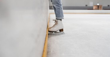 person-wearing-white-and-gray-skate-shoes-inside-ice-skating-rink